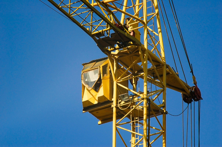 Yellow cab of a construction hoisting crane on working area in sunny day