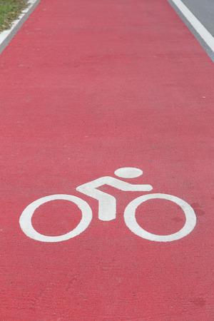 symbol sport: Fahrradweg wei�es Schild auf rotem Asphalt Lizenzfreie Bilder