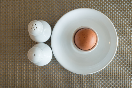 egg cups: Boiled eggs in egg cups with salt and pepper. Stock Photo