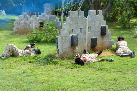 three man playing paintball sport in protective uniform Editorial