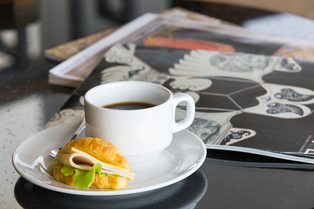 sanwich: Delicious sanwich and coffee in dish on table and the  fashion book background