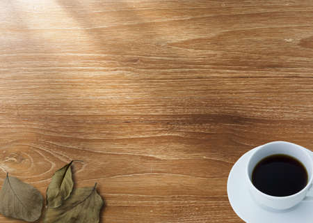 Coffee and dry leaf on wood background photo