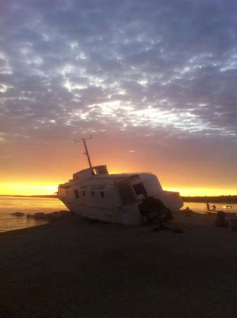 glow: Sunset at the pebble beach. Silhouette of an old oit-of-service steel ship is blocking direct sunlight. Opposed to silvery clouds the horizon is in goldn glow.