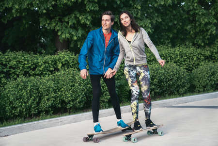A girl and a man are skateboarding