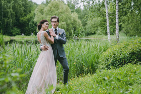 The bride and groom stand near a lake in the park Stock Photo