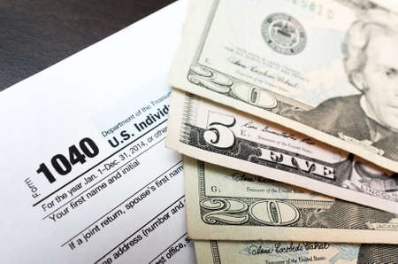 us dollars: American dollar bills and 1040 individual tax return form close up. color image in horizontal orientation Stock Photo