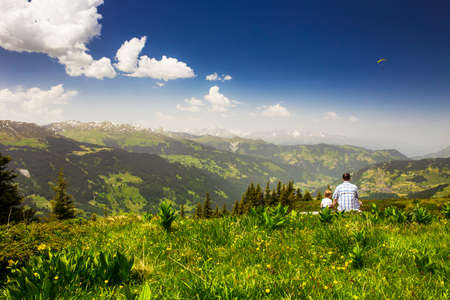 Father with his son enjoying view to Swiss Alps from the top of  Madrisa mountain, Davos, Grisons, Swirzerland