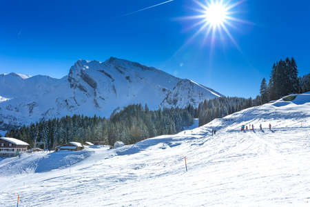 People skiing and sledging in Klewenalp ski resort in Swiss Alps, Central Switzerland