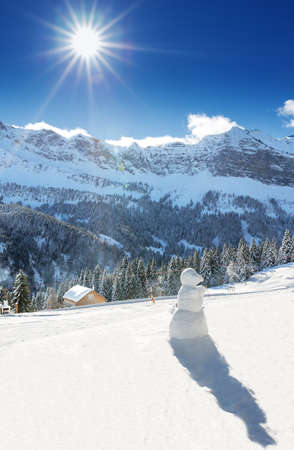 Snowman surrounded by Swiss Alps and forest in beautiful sunny weather