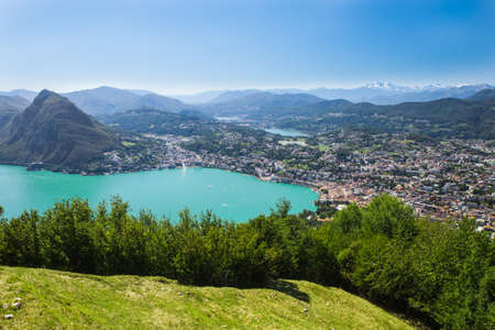 Lugano city with the view of lake Lugano and mountains seen from the Monte Bre peak