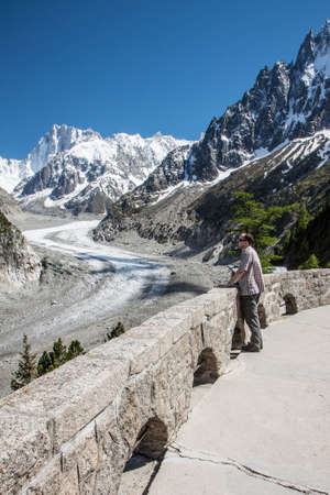 glace: Young man looking to French Alps Valley under Mt  Blanc with Mer de Glace - Sea of Ice Glacier