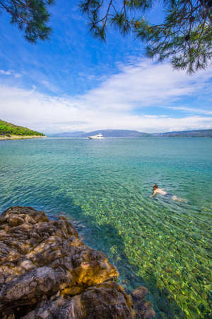Young man swimming in crystal clear tourquise sea near rocky beach on the island Cres in Croatia Stock Photo