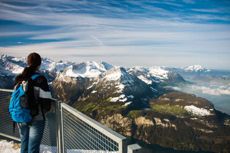 Young girl watching from the Frontalpstock peak to the Lake Lucerne - Vierwaldstattersee and Swiss Alps, Central Switzerland