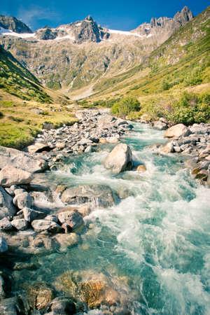 Valley with rapid stream creek in Swiss Alps near Susten mountain pass road, Switzerland