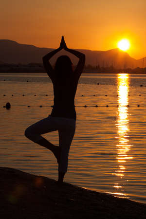 Silhouette of a beautiful woman excercising Yoga during sunset on the sea coast