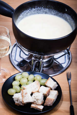 Swiss cheese fondue with bread on long-stemmed fork served with wine and grapes