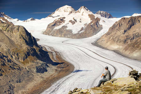 aletsch: Young man sitting and enjoying a majestic view to Aletsch glacier, the largest gracier in Alps and UNESCO herritage from Eggishorn, Valais, Switzerland, Europe Stock Photo