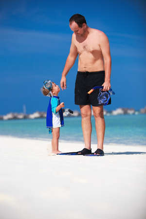snorkle: Father with his son having fun on the beach and getting ready to snorkle