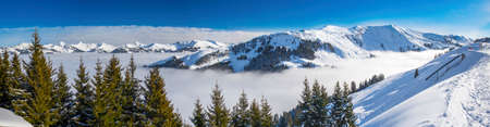 wildkogel austria: Panoramaview to ski slopes and skiers skiing in Kitzbuehel mountain ski resort with a background view to Alps in Austria freshly covered by snow, Tyrol, Austria Stock Photo