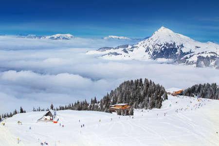 Skieur et vue sur les montagnes alpines en Autriche depuis la station de ski de Kitzbühel avec 54 téléphériques et 170 km de pistes de ski préparées, Tyrol, Autriche Banque d'images - 62094354
