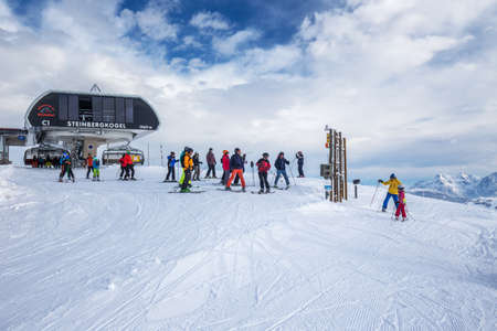 wildkogel austria: Skiers skiing in Kitzbuehel ski resort on the top of Steinbergkogrl, resort with 54 cable cars and 170 km prepared skiing slopes, place of famous hahnenkamm races, Tyrol, Austria Editorial