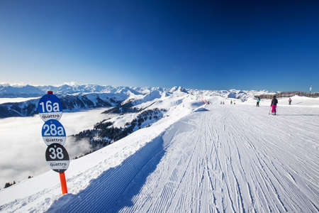 wildkogel austria: Skiers skiing in Kitzbuehel ski resort and enjoying Alps view from the top of Hahnenkamm, place of famous hahnenkamm races. Kitzbuehel ski resort is one of the best ski resort in the world with 54 cable cars and 170 km prepared skiing slopes, Tyrol, Austr