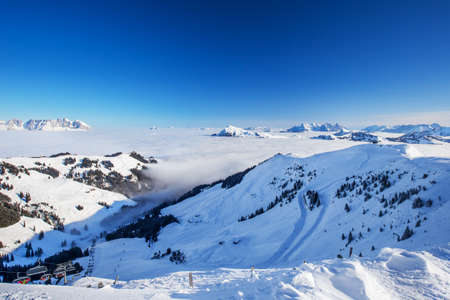 wildkogel austria: View to Alpine mountains surrounded by fog and ski slopes in Austria from Kitzbuehel ski resort with 54 cable cars, 170 km prepared skiing slopes and place of famous hahnenkamm races, Tyrol, Austria Editorial