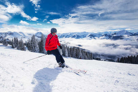 Young happy man skiing in Kitzbuehel ski resort and enjouing the beautiful weather with blue sky and Alpine mountains, Tyrol, Austria 免版税图像