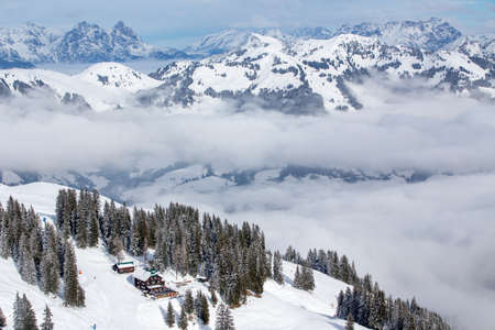 wildkogel austria: Skier skiing and enjoying the view to Alpine mountains in Austria from Kitzbuehel ski resort with 54 cable cars and 170 km prepared skiing slopes. Editorial