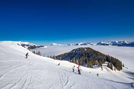 wildkogel austria: Skier skiing and enjoying the view to Alpine mountains in Austria from Kitzbuehel ski resort - one of the best ski resort in the workd with 54 cable cars, 170 km prepared skiing slopes and place of famous hahnenkamm races, Tyrol, Austria