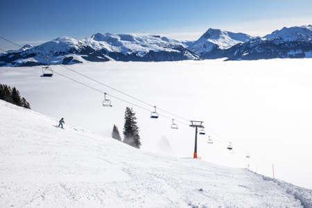 wildkogel austria: Skiers on ski lift enjoying the view to foggy Alps in Austria and beautiful snowy country panorama in famous Kitzbuehel mountain ski resort, Tyrol, Austria