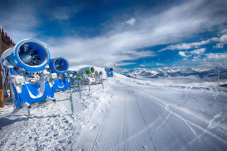 Snow cannons with fresh prepared ski slopes with the corduroy pattern in Kitzbuehel ski resort, Tyrol, Austria