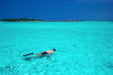 snorkelling: Young man snorkelling in the Maldives lagoon with overwater bungalows