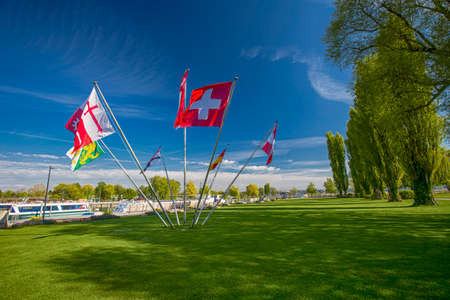 Swiss and cantonal flags in the centre of park in Kreuzlingen with the  lake Constance in the background, Switzerland.