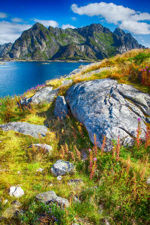 View to Norwegian mountains in Henningsvaer, Lofoten, Norway. Lofoten is known for a distinctive scenery with dramatic mountains, open sea and sheltered bays, beaches and untouched lands.