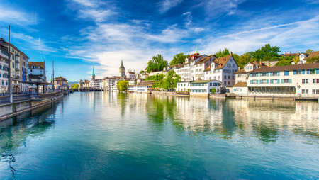Beautiful view of the historic city center of Zurich with famous Fraumunster Church and swans on river Limmat on a sunny day with blue sky, Canton of Zurich, Switzerland Stock Photo