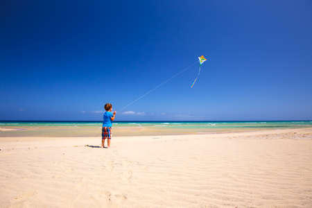 Happy little boy playing with kite on the beach, Fuerteventura, Canary Island, Spain.