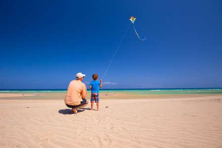 teen golf: Padre y su pequeño hijo jugando con una cometa en la playa.