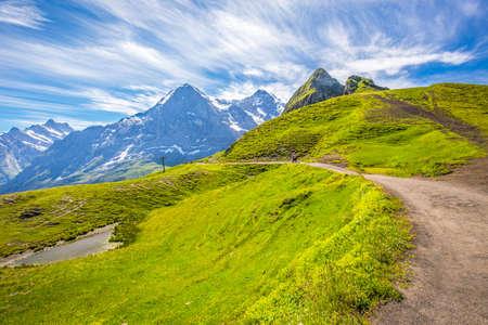 monch: Panorama trail leading to Kleine Scheidegg from Mannlichen with Eiger, Monch and Jungfrau mountain (Swiss Alps) in the background, Berner Oberland, Grindelwald, Switzerland. Stock Photo