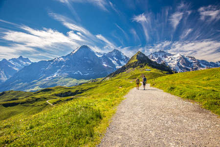 Young couple hiking in panorama trail leading to Kleine Scheidegg from Mannlichen with Eiger, Monch and Jungfrau mountain (Swiss Alps) in the background, Berner Oberland, Grindelwald, Switzerland. Stock Photo