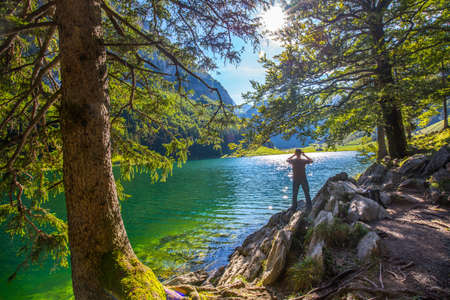 appenzeller: Young man photographing Seealpsee with the Swiss Alps (mountain Santis), Appenzeller Land, Switzerland