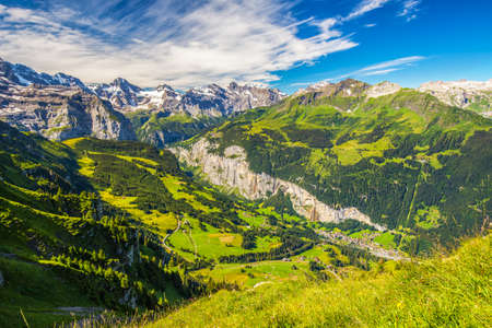 Famous Lauterbrunnen valley with gorgeous waterfall and Swiss Alps in the background from Mannlichen, Berner Oberland, Switzerland, Europe.