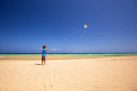teen golf: Little boy flies a kite on a beach. Foto de archivo