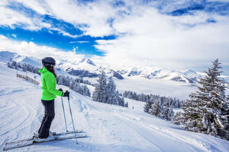 wildkogel austria: Young woman skiing in Kitzbuehel ski resort and enjoying the beautiful weather with blue sky and Alpine mountains in Tyrol, Austria