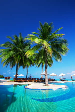 Swimming pool on the beach of tropical island with white beach umbrellas and chairs Editorial