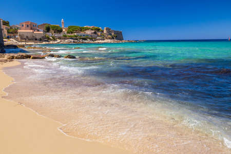 View to beautiful Algaloja old town and sandy beach with turquoise clear water, Corsica, France, Europe.