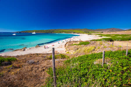 People enjoying the sunny weather on sandy Grand Capo beach with red rocks near Ajaccio, Corsica, Europe.