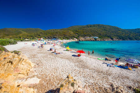 People enjoying the sunny weather on sandy Petit Capo beach with red rocks near Ajaccio, Corsica, Europe.