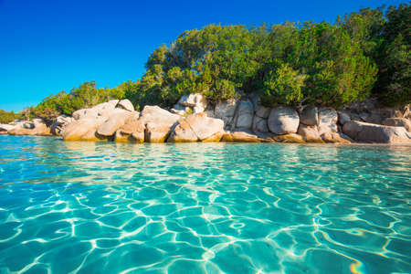 spiaggia di Santa Giulia con rocce rosse, pini e azzurro acqua limpida, Corsica, Francia.