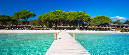 CORSICA, FRANCE - August 29, 2016 - Bidge leading to beach resort in Santa Giuliana beach with pine trees and azure clear water, Corsica, France, Europe.